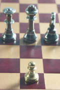 Gold pawn on red and brown chess board with silver king queen a 2