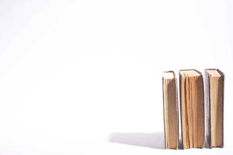 Hardcover books with yellowed pages standing on end